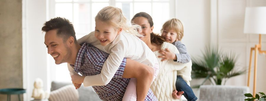 Happy loving dad piggybacking little daughter playing with family at home, smiling parents carrying kids on back, children boy and girl having fun together enjoying ride during active game on weekend